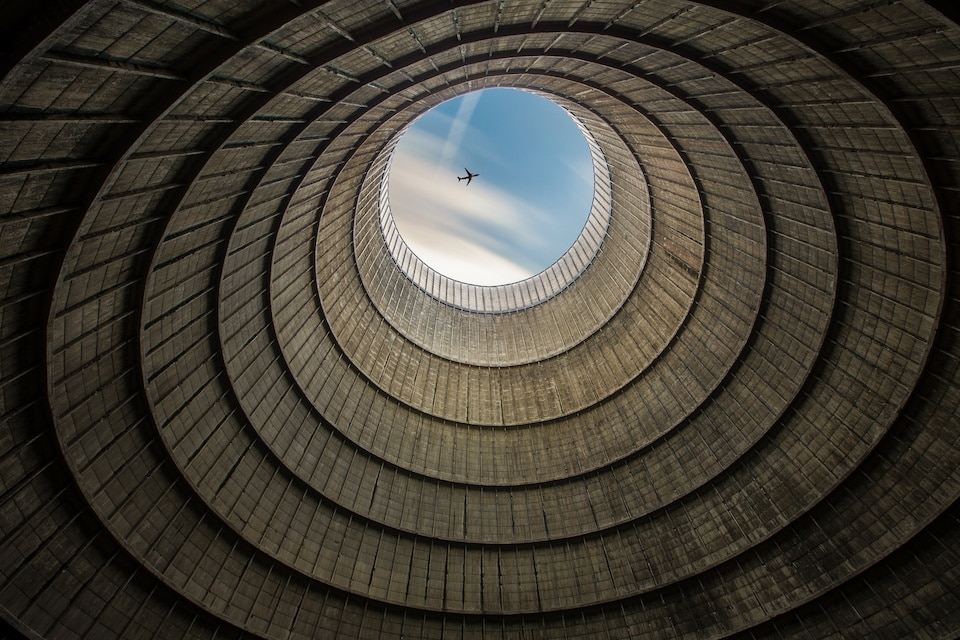 Article featured image showing an airplane through the mouth of a nuclear power plant.