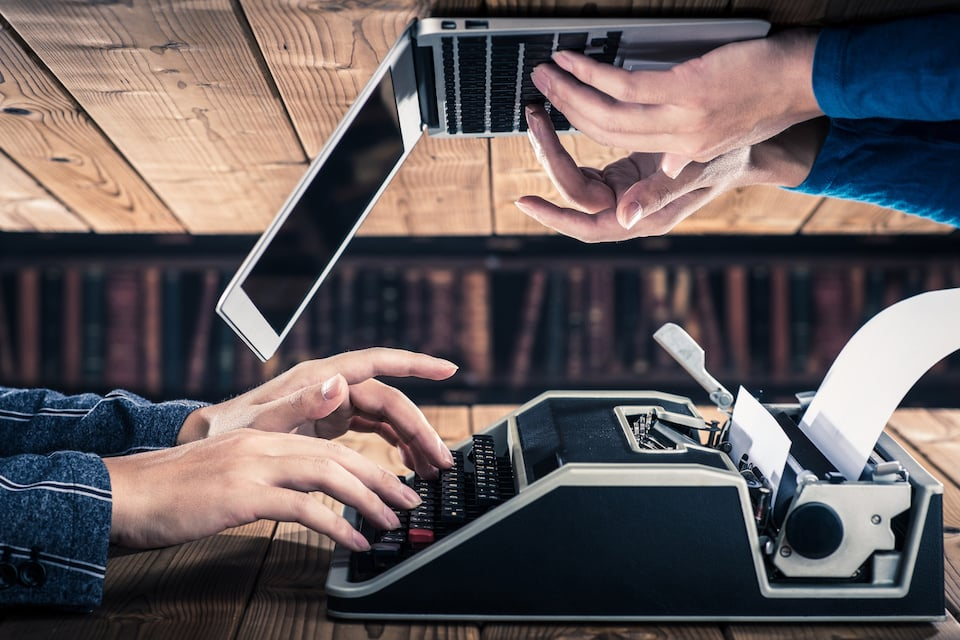 Article featured image showing hands typing on an old typewriter and on a modern laptop.