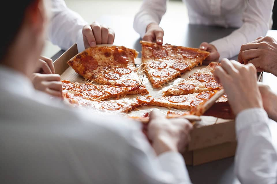Article featured image showing business people sharing a pizza metaphorically referring to community shared moments